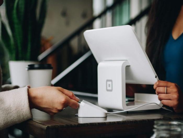 reception desk hands processing credit card on computer